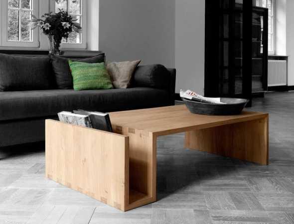 שולחן מעץ מלא שצורתו הייחודית מאפשרת לאחסן מגזינים ועיתונים ובו בזמן להשאיר את השולחן מסודר ונעים.