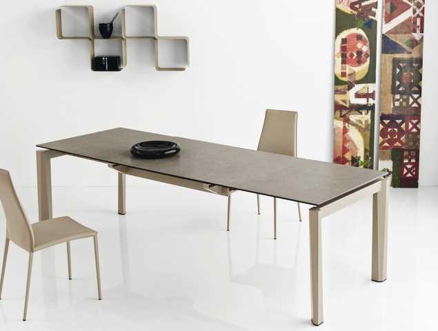 שולחן נפתח בעל בסיס מתכת ומשטח עליון מזכוכית או קרמיקה. ניתן להזמין במגוון מידות וחומרים.