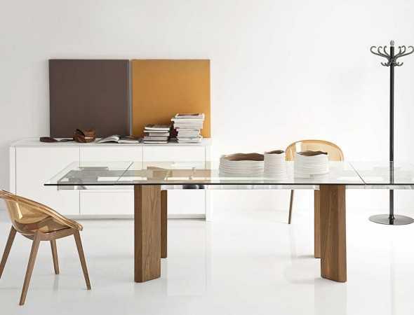 שולחן נפתח בעל בסיס עץ ומשטח עליון מזכוכית. ניתן להזמין במגוון מידות וחומרים.