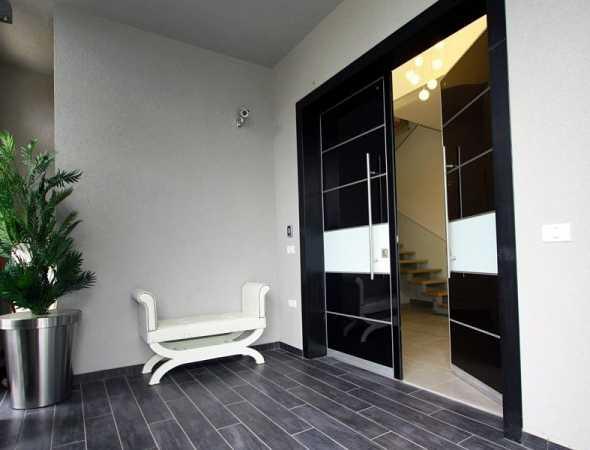 דלת כניסה מעוצבת המשדרת דרמטיות ומעניקה עוצמה לכניסה לבית, עם חיפוי של לוחות אלום וגוון שחור מבריק, השילוב הרמוני וכובש ולוקח את ההצגה.