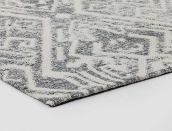 שטיח מיוחד העשוי משילוב של סיבי ויסקוזה, כותנה וצמר איכותיים ונעימים. השטיח מעוצב בסגנון מודרני של צורות גיאומטריות אלכסוניות בגווני אפור בהיר.