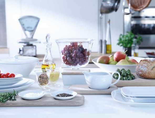 כלי הגשה בשילוב מגשי עץ, צלחות וקערות מפורצלן, כלי לשמן ומשקל למטבח