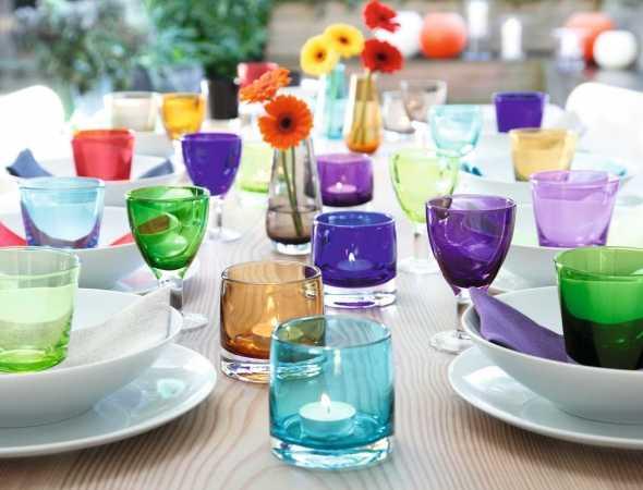 פמוטים נמוכים, וואזות וכוסות במגוון צבעים עשויים מזכוכית בעבודת יד בשילוב עם צלחות מפורצלן