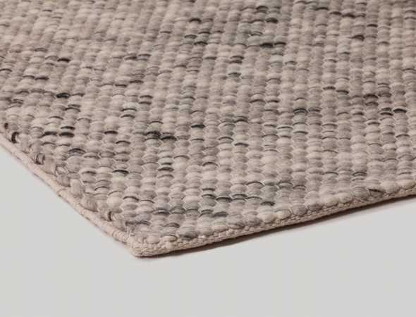 שטיח העשוי מחוטי צמר המשלבים צבעים לבנים, שחורים ואפורים בפיזור אקראי