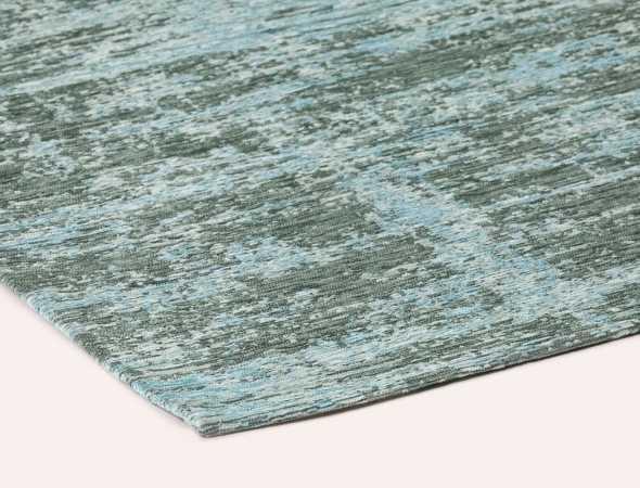 שטיח אבסטרקט מיוחד בגווני טורקיז וירוק היוצרים מראה ייחודי ומודרני