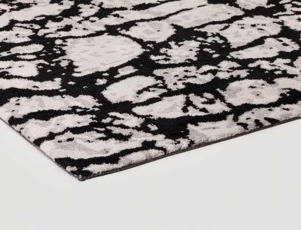 שטיח בגוונים שחור ובז' עשוי ממיקרו פייבר נעים למגע וקל לתחזוקה.