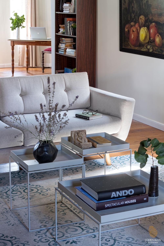 הסלון אשר ממוקם בעומק הבית מייצר דרמה בחלל בשל המרחק שלו מהכניסה והתקרה החשופה שמיד תופסת את העין עם גופי תאורה וריהוט מודרני.